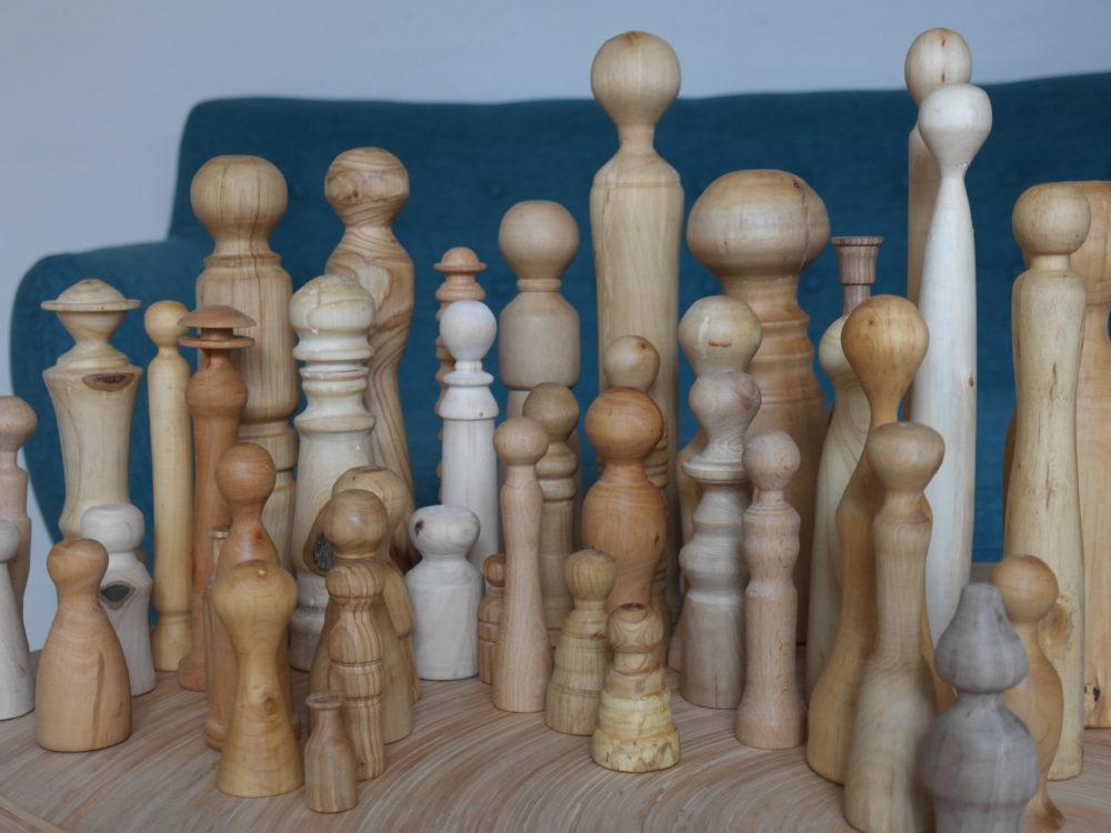 Stellfiguren für die Familientherapie auf einem Holztisch. Im Hintergrund befindet sich eine weiße Wand.