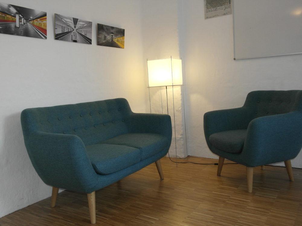 Zwei Sessel angeordnet für Institutionen. In diesen Sesseln werden Menschen beraten. Im Hintergrund sind 3 Gemälde zu sehen.