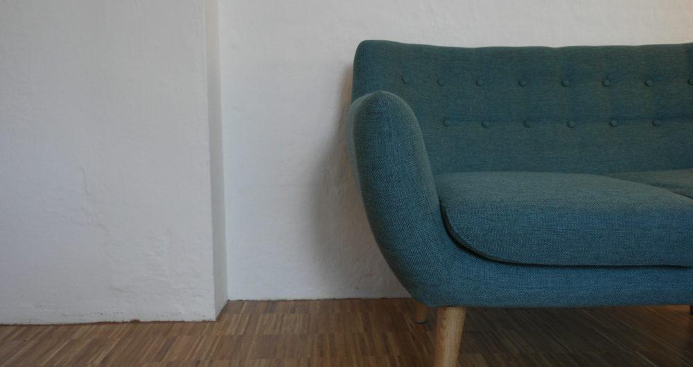 Supervision Heimbach in der Praxis Zeitraum mit weißer Wand und blauen Sofa.
