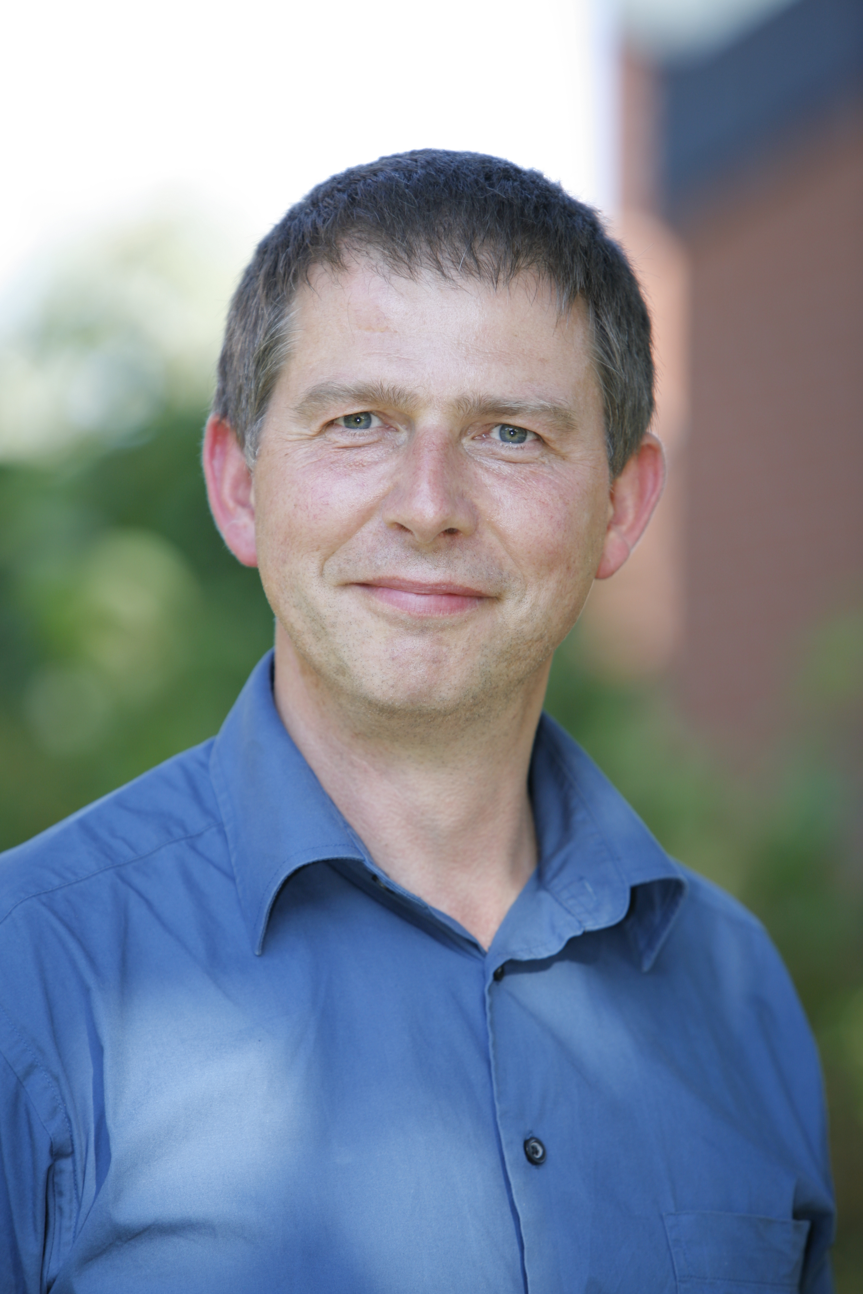 Zu sehen ist Andreas Heimbach im blauen Hemd vor der Praxis Zeitraum
